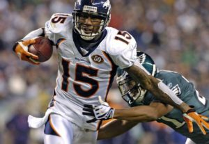 Brandon Marshall stiff arms a defender while playing wide receiver for the Denver Broncos