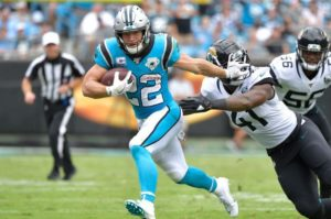 Christian McCaffery of the Carolina Panthers stiff arms a defender as he runs down the field