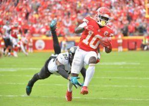 Tyreek Hill of the Kansas City Chiefs running away from a defender