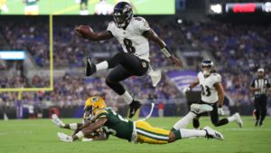 Lamar Jackson, quarterback for the Baltimore Ravens, jumping over a defender en route to a touchdown