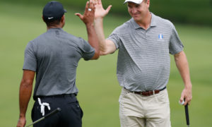 Peyton Manning high fives Tiger Woods during a golf game